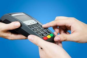hand med kreditkort svepa genom terminalen till salu foto