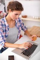 le kvinna online shopping med dator och kreditkort i foto