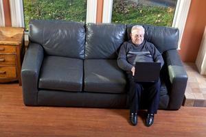 äldre man som arbetar på bärbar dator foto