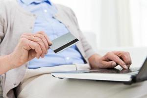 äldre kvinna med laptop och kreditkort hemma foto