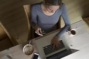 kvinna som använder bärbar dator för att göra en kortbetalning foto