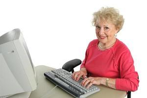 äldre dam tycker om dator foto