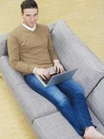 man på soffan med bärbar dator foto