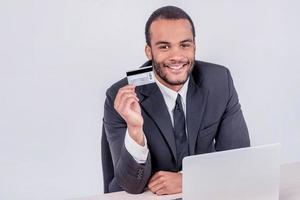onlineförsäljning. framgångsrik afrikansk affärsman som sitter vid en bärbar dator foto