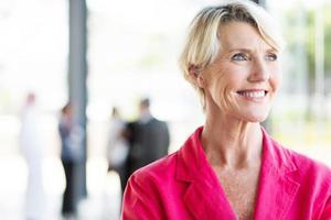 äldre affärskvinna som står vid kontorsfönstret foto