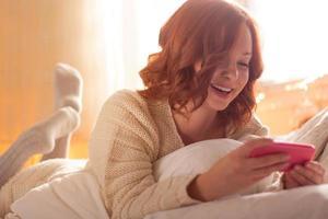 rödhårig kvinna skrattar och smsar medan hon ligger i sängen foto