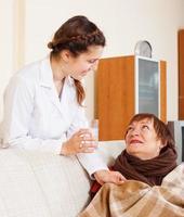 vårdande sjuksköterska som ger ett glas vatten till den mogna kvinnan foto