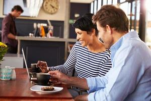 man och kvinna möter över kaffe på en restaurang foto