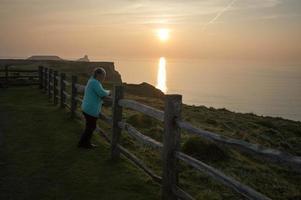 mogen kvinna tittar på solnedgången på rhosilli foto
