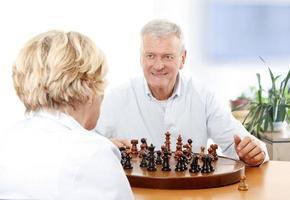 äldre par som spelar schack foto