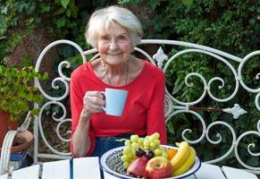 gammal kvinna som har en kaffe i trädgården. foto