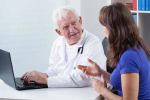 kvinna som besöker erfaren läkare foto