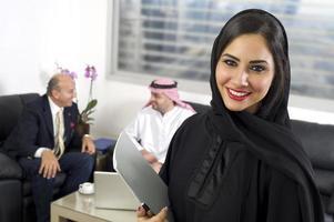 arabisk affärskvinna med affärsmän som möts i bakgrunden foto