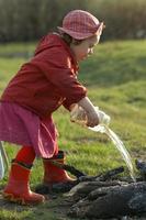 tre år gammal flicka häller vatten eld foto
