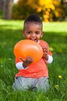 utomhus porträtt av en söt ung liten svart pojke som spelar foto