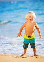 ung pojke som leker på stranden foto