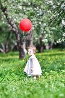 rolig baby flicka som leker med en stor röd ballong foto