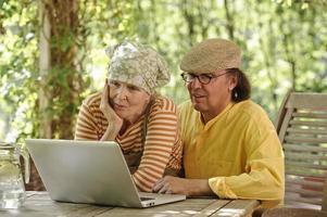 äldre par tittar på bärbar datorskärm foto