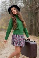 stående attraktiv tjej med en resväska i naturen foto