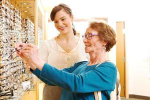 optiker som hjälper äldre dam med glasögon foto