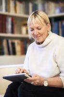 äldre kvinna använder pekplatta enhet foto