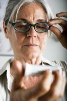 äldre kvinna läser medicin foto
