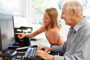 äldre man och barnbarn använder dator foto
