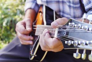äldre man spelar mandolin