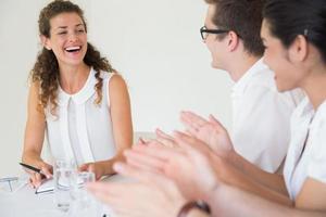 affärsfolk applåderar för affärskvinna foto