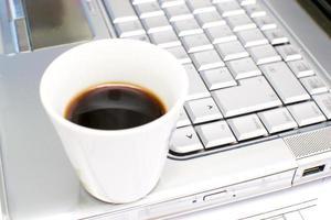 dator och kaffe på kontorsbordet foto
