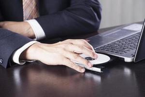 affärsman infoga disk till bärbar dator foto