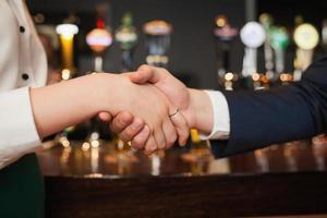 närbild på kollegor som skakar hand foto