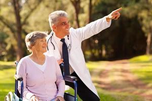 vänlig läkare och äldre patient utomhus för en promenad foto