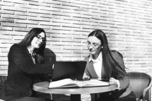två affärskvinnor som tittar på en bärbar dator som gör något lagarbete foto