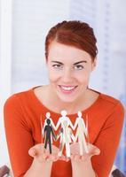 vacker affärskvinna innehar team av pappersfolk i office foto