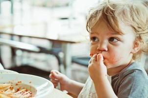 småbarn äter pasta foto
