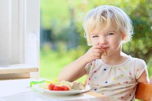 liten flicka som har pasta med tomater till lunch foto