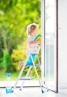 söt barnflicka tvättar ett fönster foto
