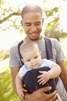 far med son i bärare som går genom parken foto