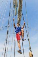 ung sjöman som klättrar på masten på det höga skeppet. foto