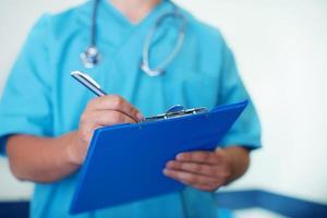 läkare skriver ner på medicinska diagram foto