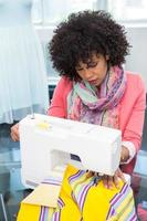 modedesigner med symaskin foto