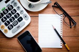 blank sida anteckningsbok och miniräknare med smart telefon foto