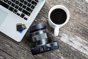 bärbar dator med digital kamera och en kaffekopp. foto