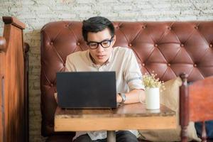 affärsman som sitter i kafé med bärbar dator foto