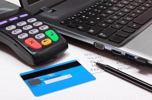 betalningsterminal med kreditkort, bärbar dator och finansiella beräkningar foto