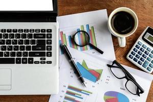 bärbar dator på skrivbordskontor och grafikanalys kalkylblad, företag f foto