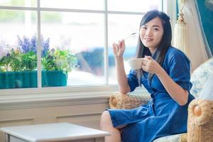 ung asiatisk kvinna som dricker kaffe på caféet foto