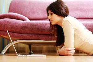 ung vacker kvinna som ligger på golvet med laptop foto