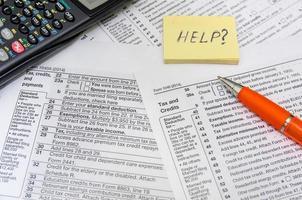 beskattning koncept: form med miniräknare, pengar, penna foto